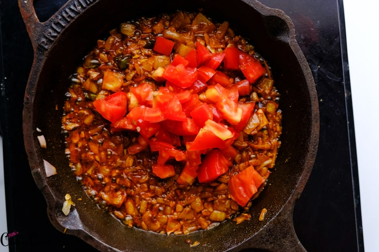 chopped tomato with spices are in cast iron pan