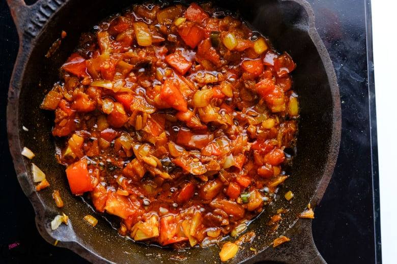 onion tomato masala are in cast iron pan