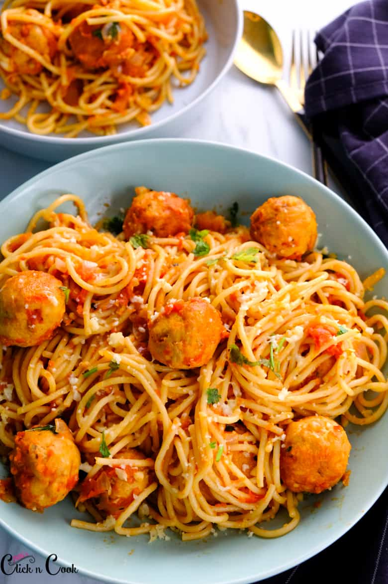 spaghetti and meatballs served in green bowl