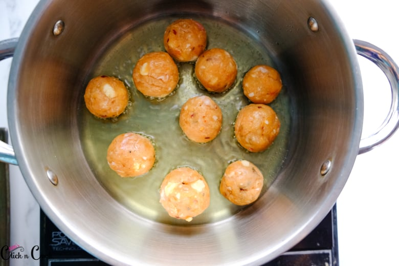 chicken meatballs are fried in oil in sauce pan