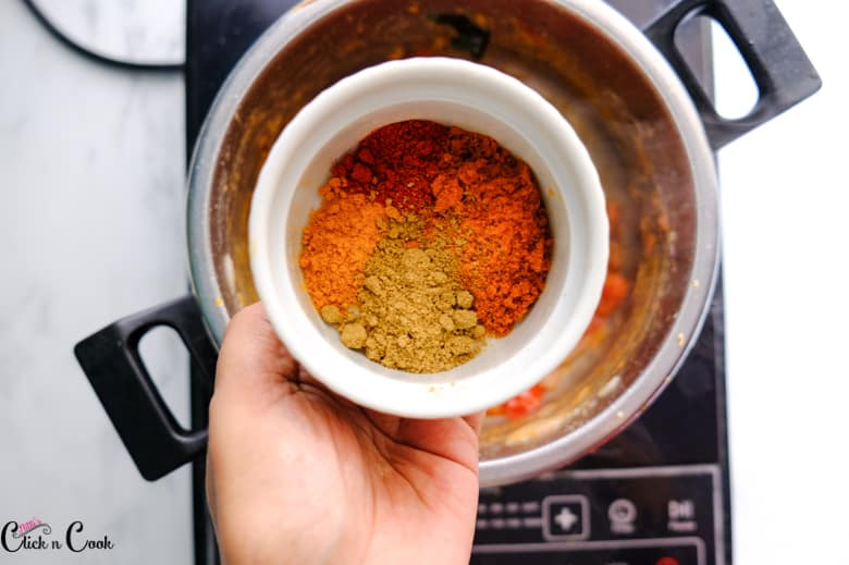 spice powders in white bowl is being added to pan