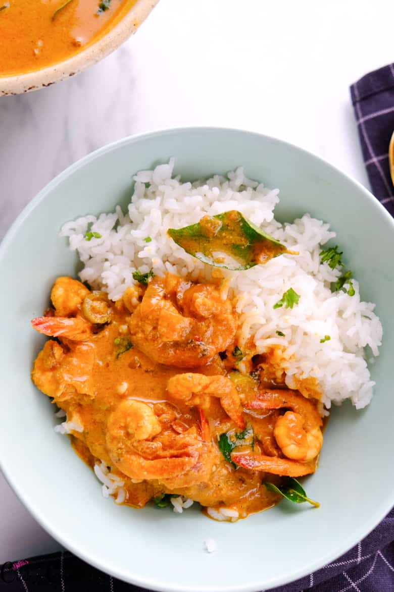 goan prawn curry served over the rice in green bowl
