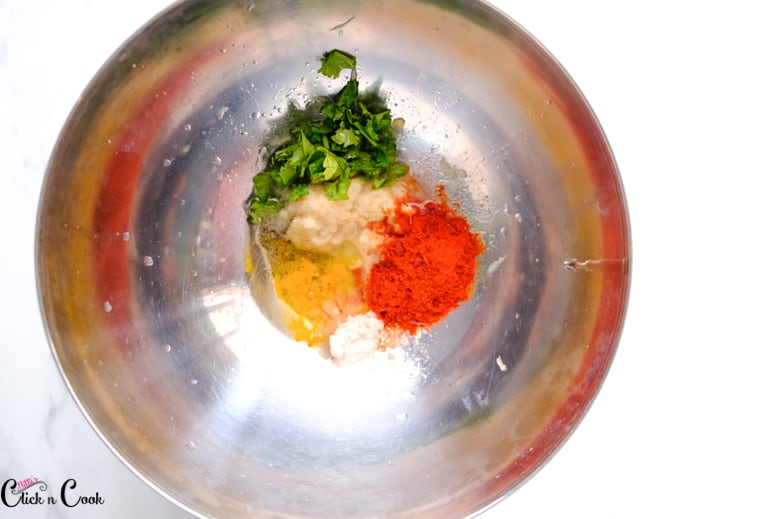 ginger garlic paste, chilli powder and spices are in steel mixing bowl