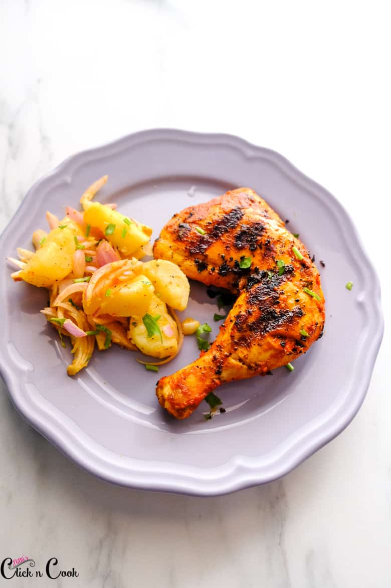 grilled chicken served in grey plate with potato salad aside.