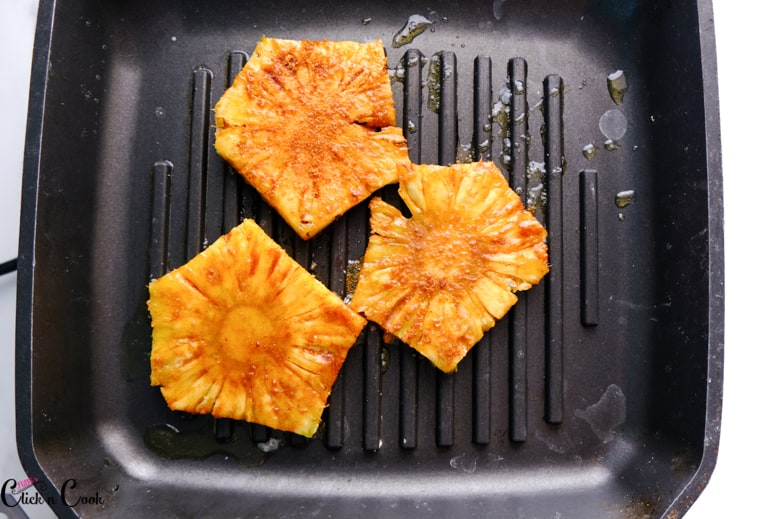 Pineapple slices are on the grill pan