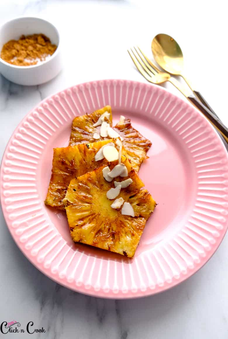 close up shot of grilled pineapple recipe topped with sliced almonds served in pink plate with fork and spoon aside
