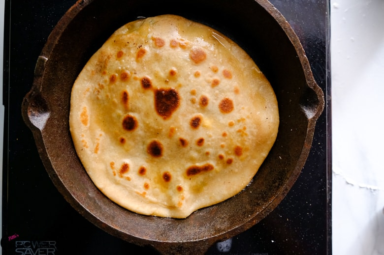 paneer stuffed paratha is cooked on the pan