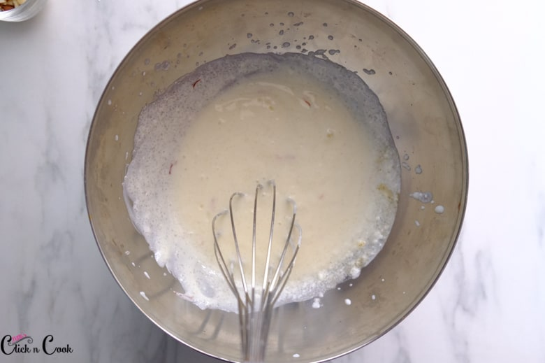 yoghurt is being whisked in a steel bowl using balloon whisk.