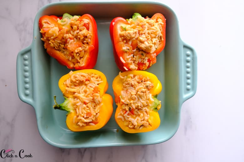 stuffed peppers are in the blue baking pan