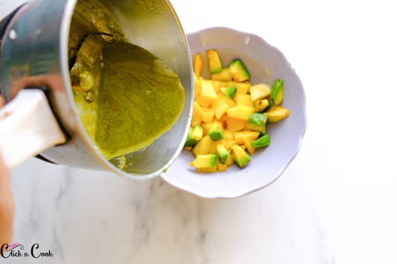cilantro lime sauce is being added to chopped mango in the grey bowl