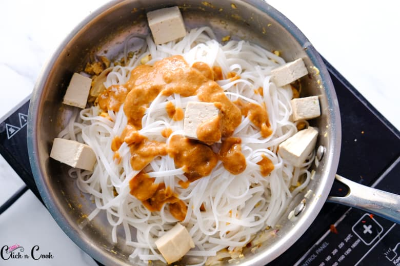 pad thai noodles, tofu and sauce are in the pan