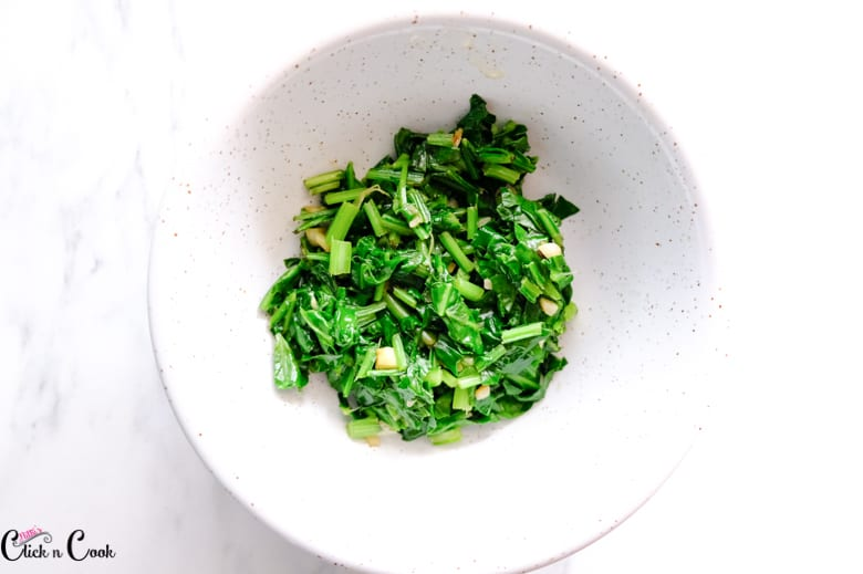 cooked spinach in white bowl